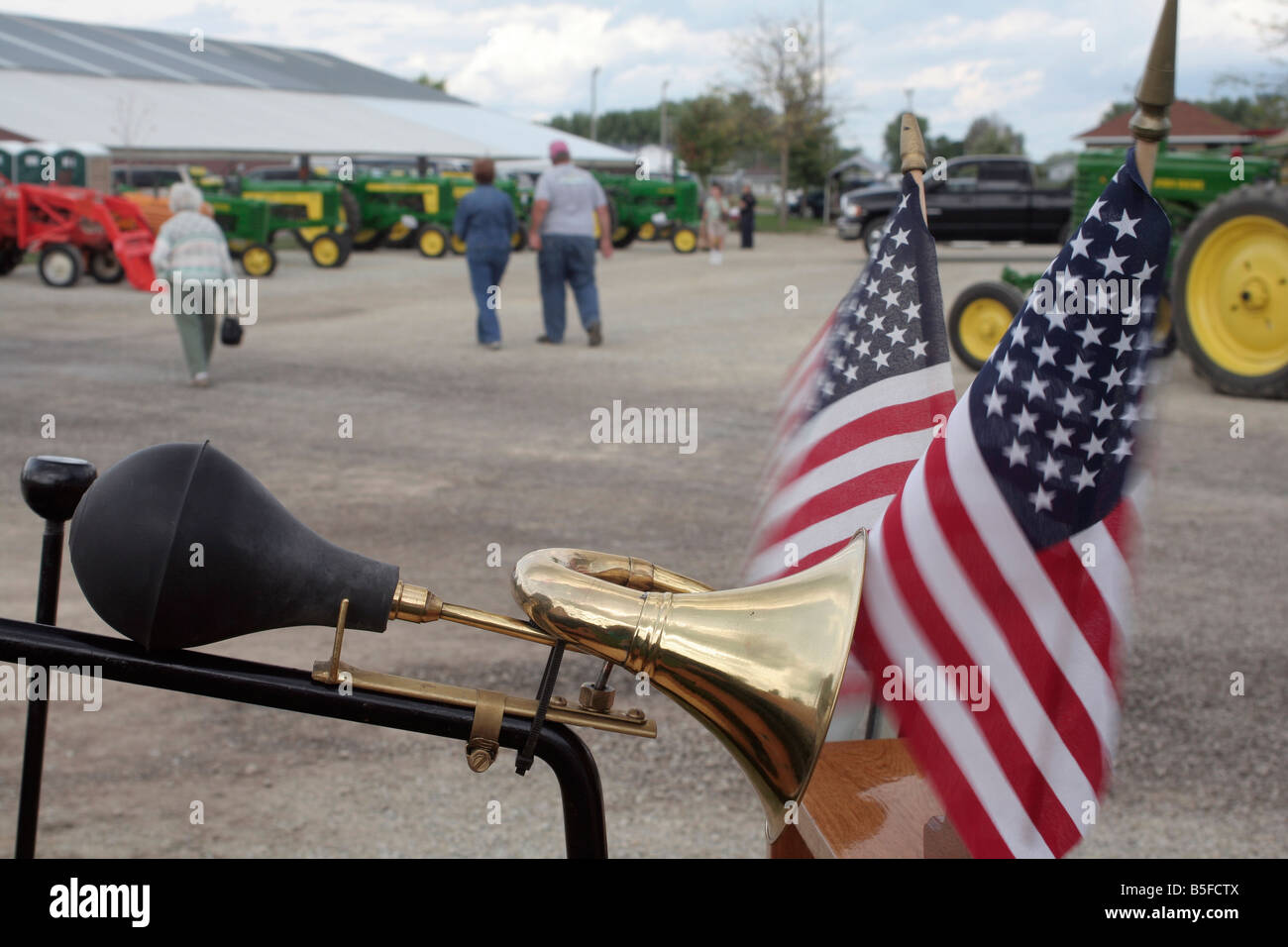 Old brass automobile horn and American flags - Stock Image