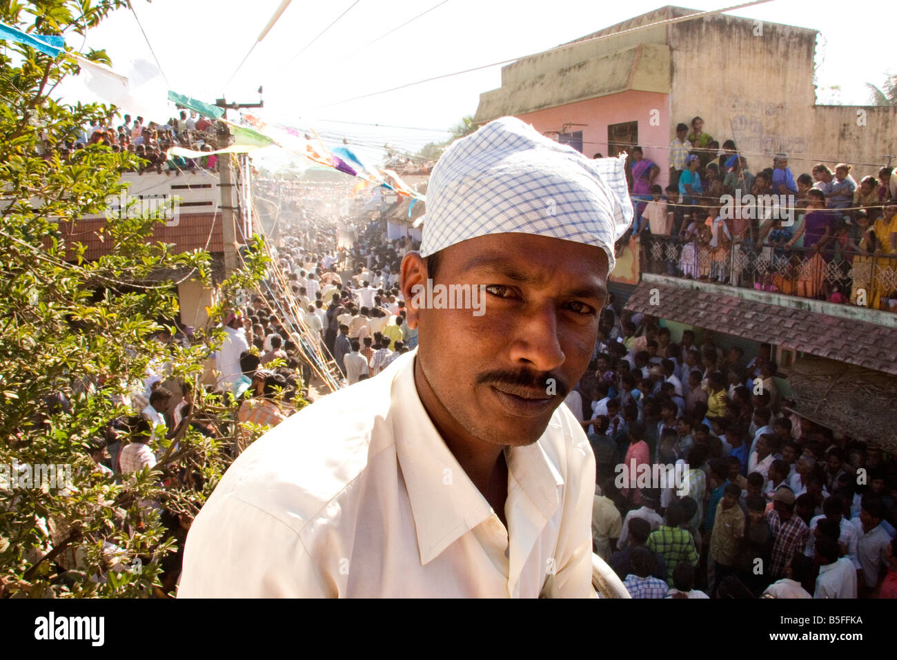 A man stands among people cram onto a roof under live electricity wires to watch bull racing. - Stock Image