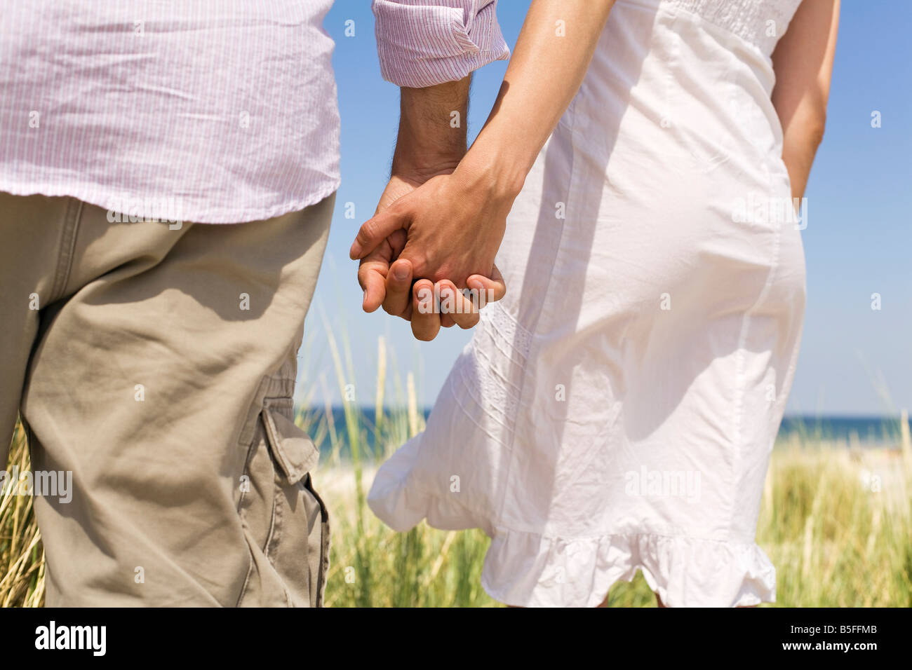Germany, Baltic sea, Couple holding hands, rear view Stock Photo