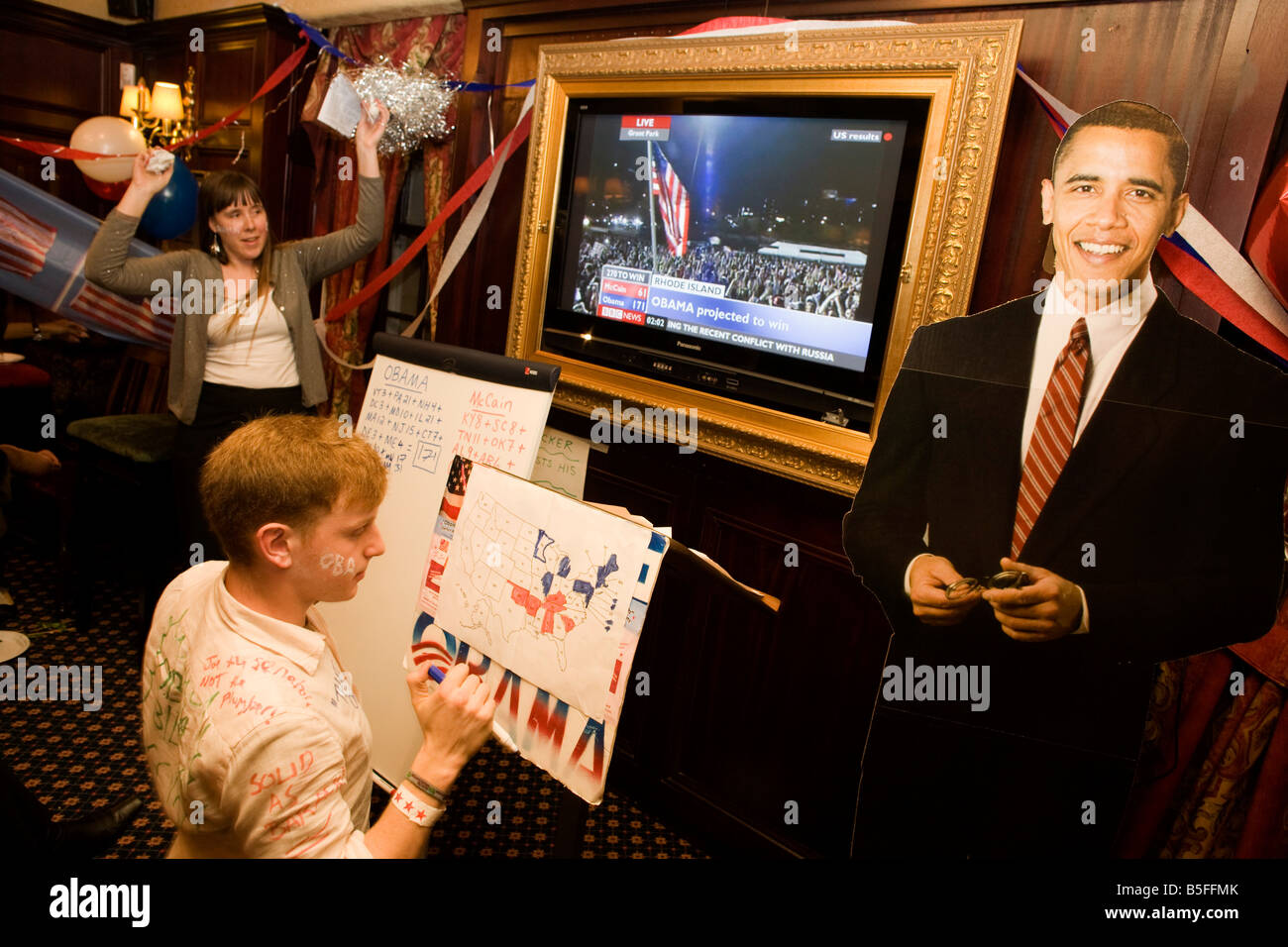 Democrat Party members keep up with latest results with life-size cardboard cut-out of Barack Obama during 2008 - Stock Image