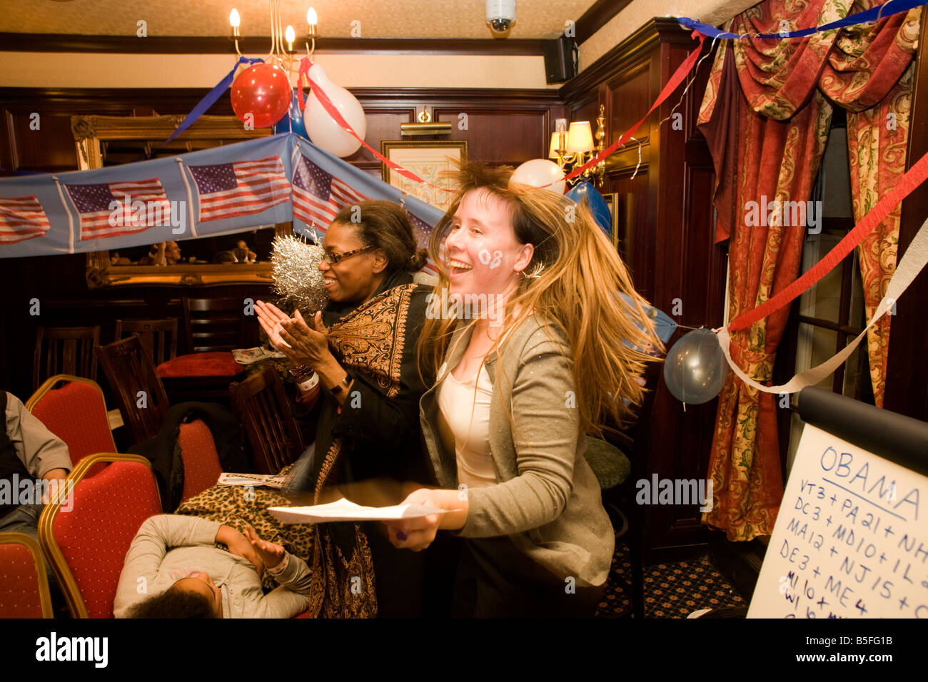 Democrat members celebrate as Barack Obama is declared winner of another US state during overnight election party - Stock Image