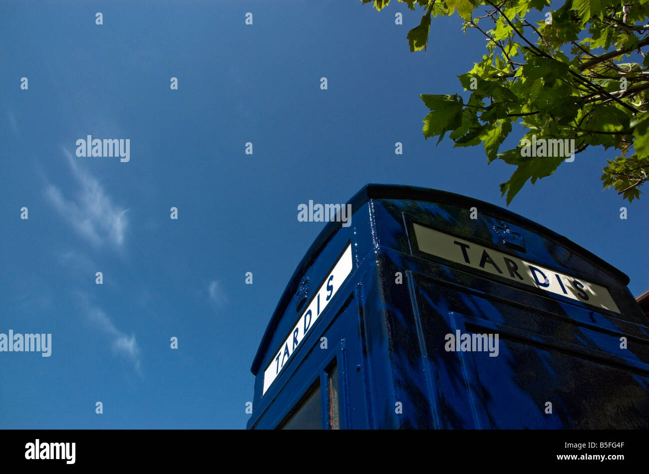 An old english telephone booth painted blue as a tardis - Stock Image