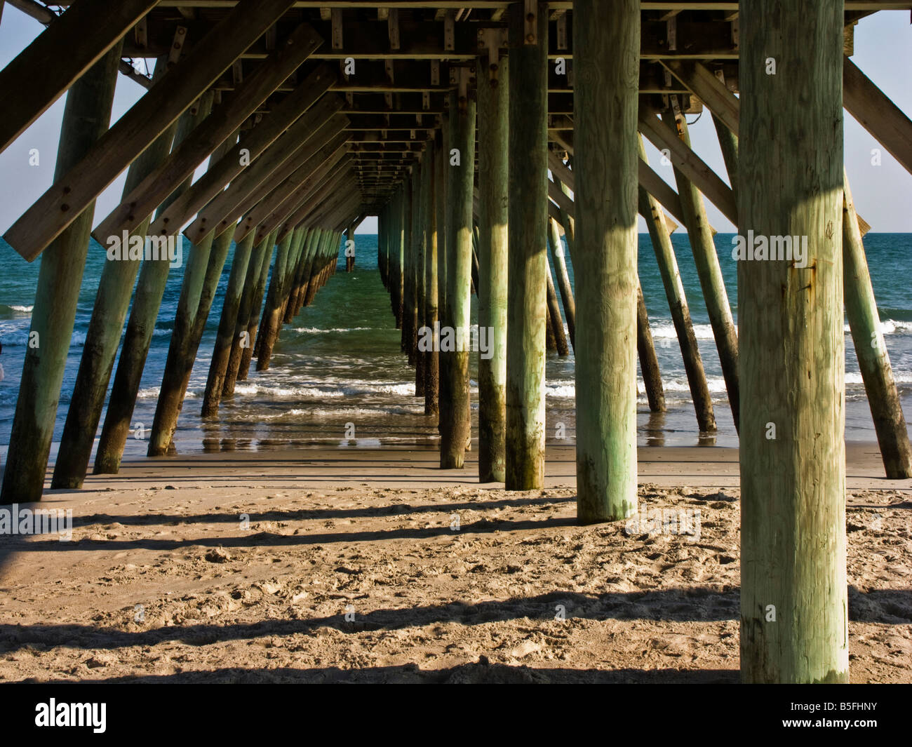 Massive wooden posts support the pier at Myrtle Beach State Park in South Carolina. - Stock Image