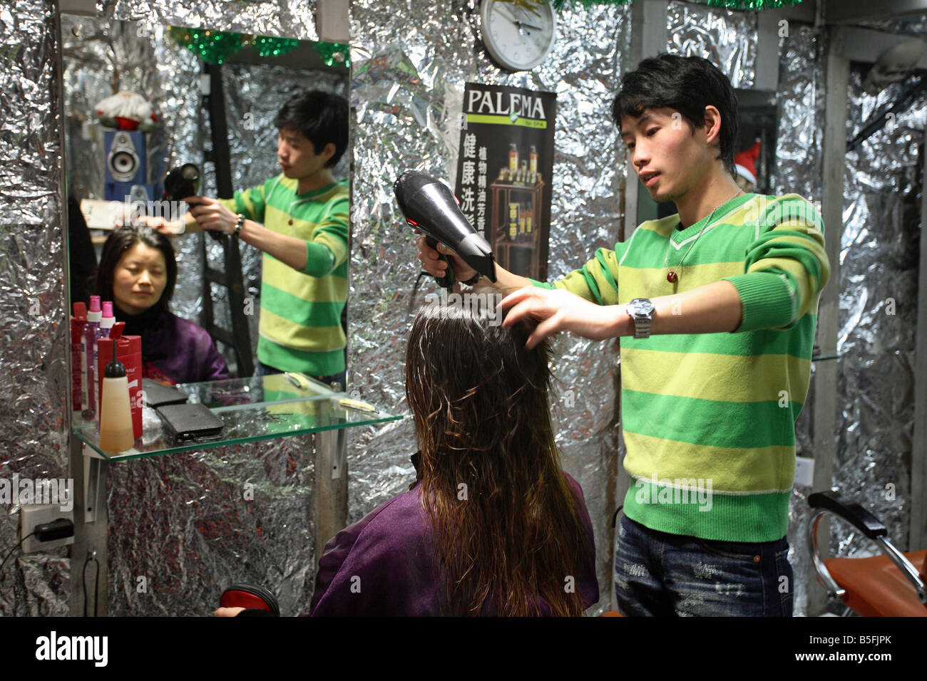 A hairdresser drying hair, Shanghai, China - Stock Image