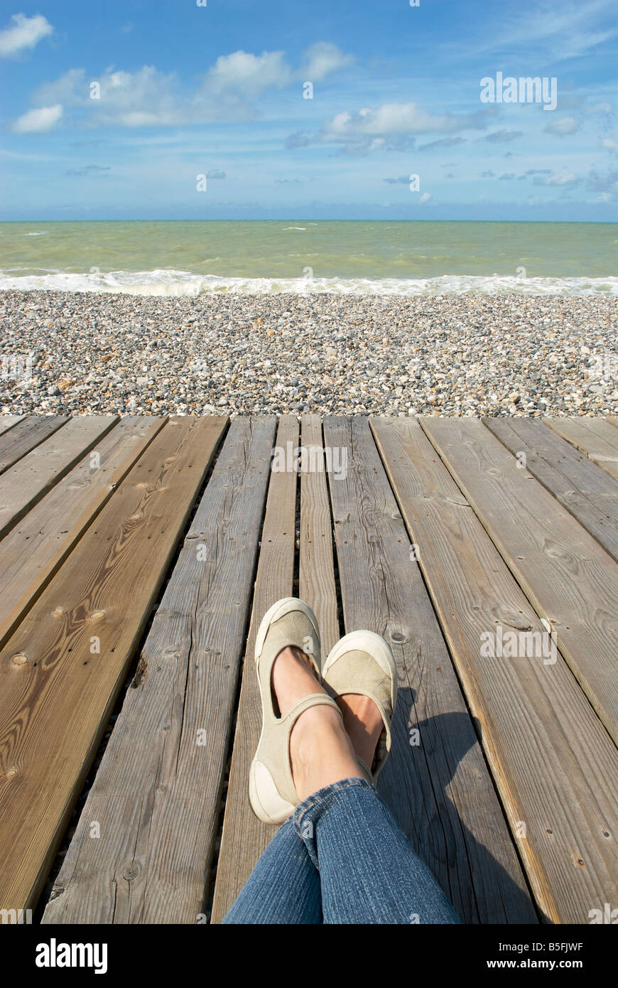 View of two legs and feet relaxing on a board walk beside a pebbled beach and ocean - Stock Image
