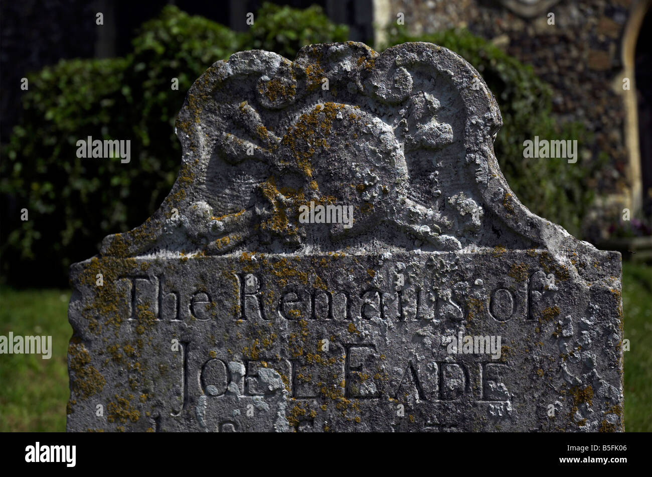 An old gravestone with a skull and crossbones motif in Saxmundham - Stock Image