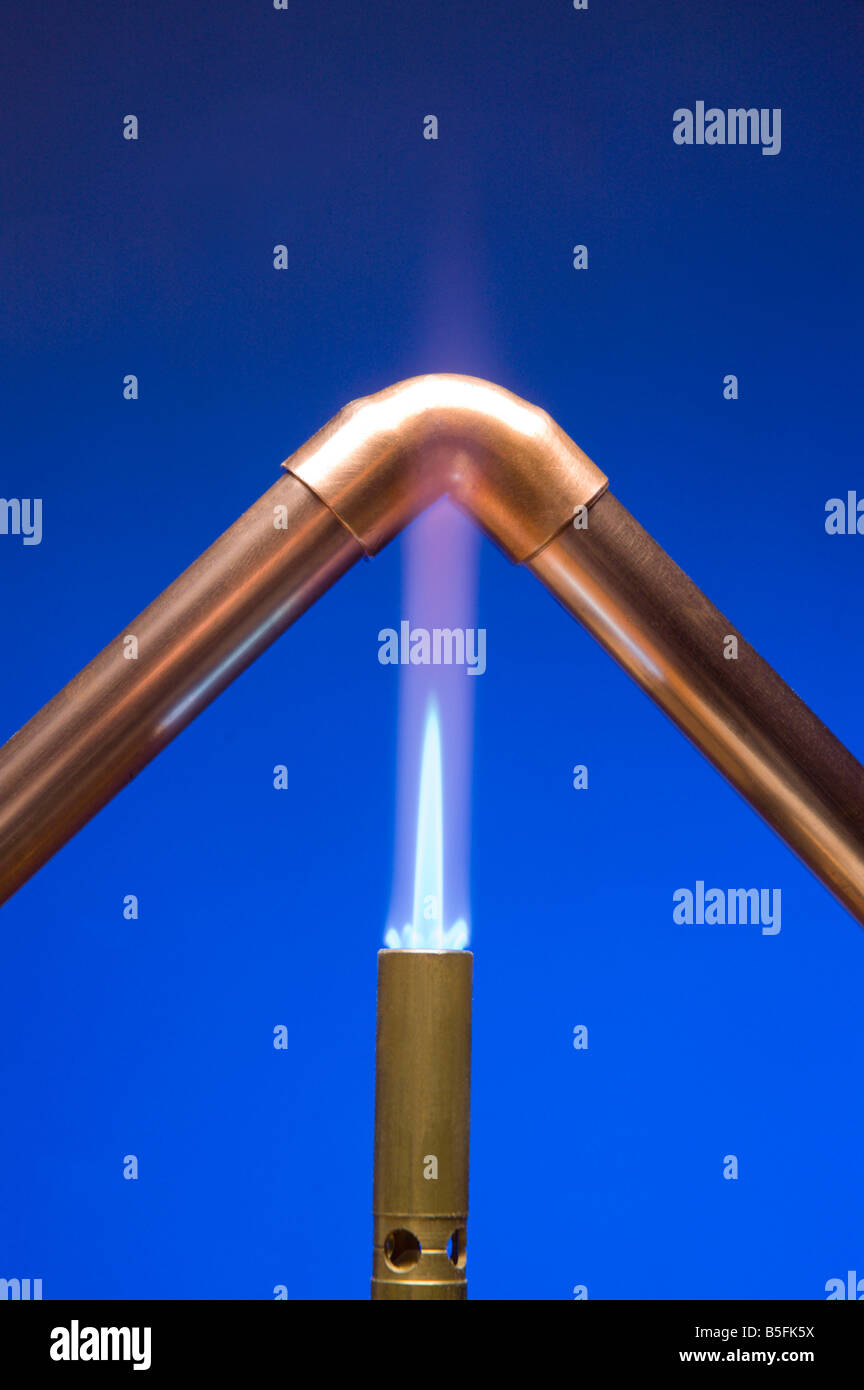 Copper elbow join heated up for soldering - Stock Image