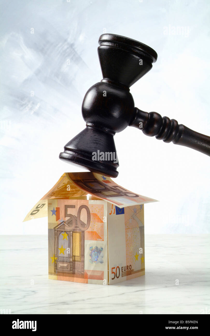 Fifty-euro notes shaped into a house and an auction hammer Stock Photo