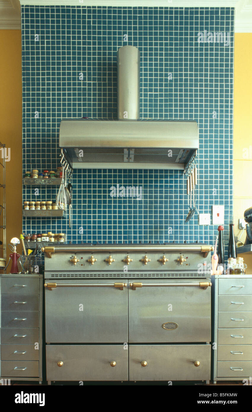 Stainless steel extractor fan on blue mosaic tiled wall above steel ...