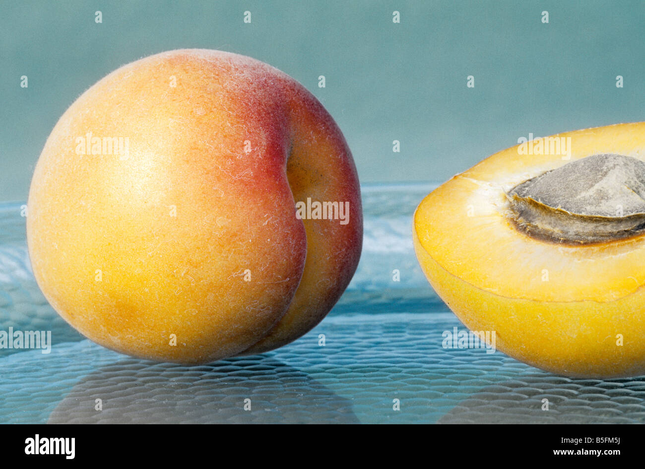 Apricots on glass plate - Stock Image