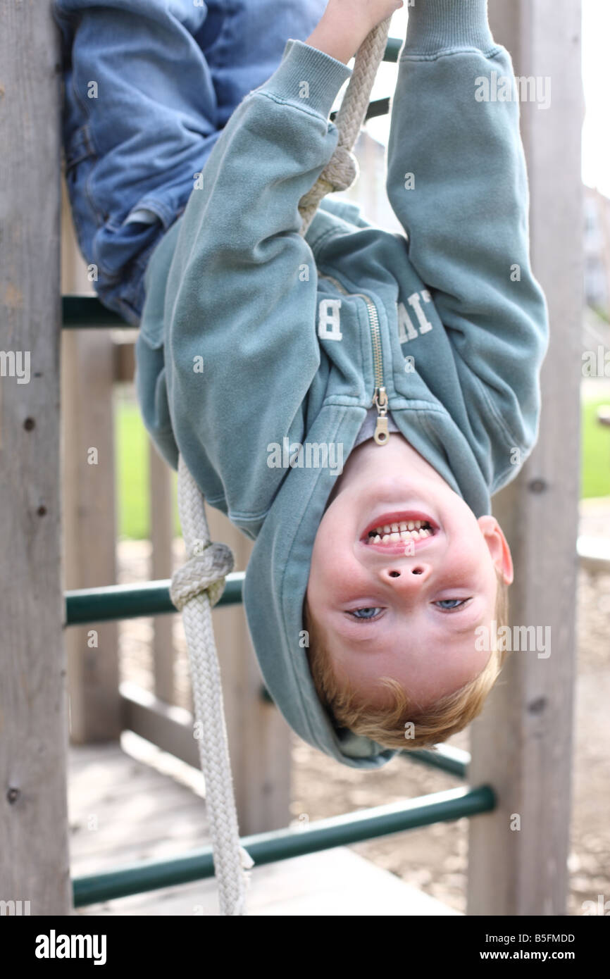Boy hanging upside down on play structure - Stock Image