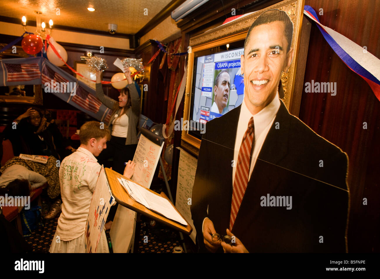 Democrat Party member keeps up with latest results with life-size cardboard cut-out of Barack Obama during 2008 - Stock Image