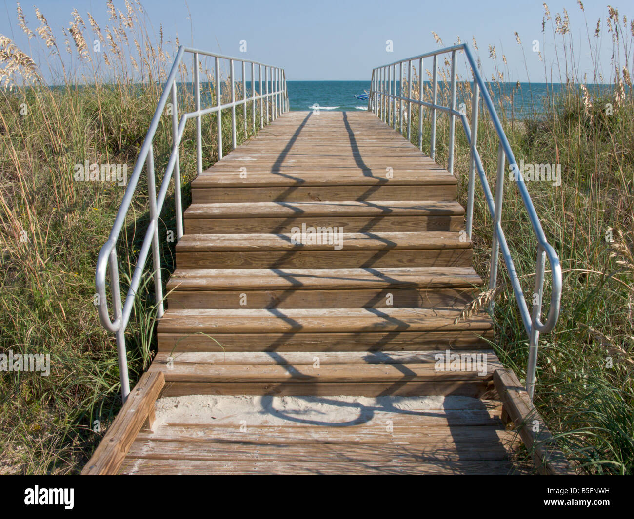 A wooden stairway and boardwalk leads across the sand dunes to the main beach at Myrtle Beach State Park, South - Stock Image
