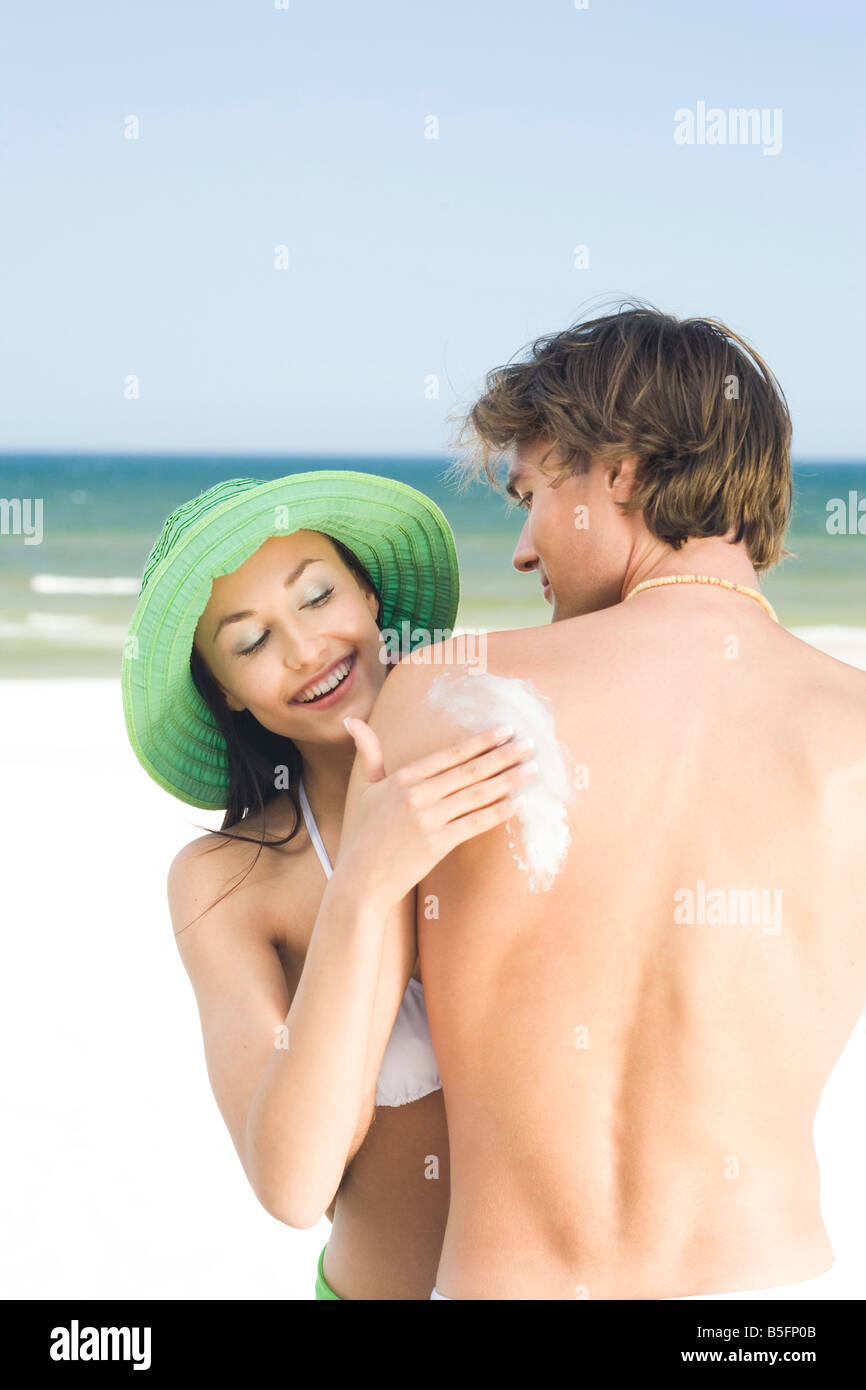 woman applying suntan lotion on mens back - Stock Image