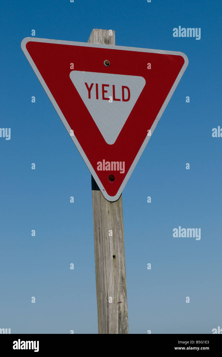 a yield sign against a blue sky - Stock Image