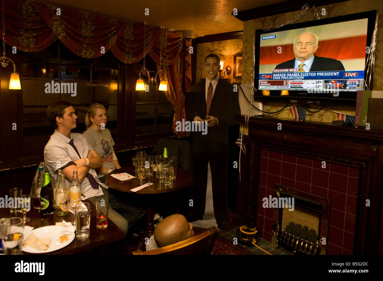 Young couple watch John McCain concede defeat by life-sized cut-out of Barack Obama after overnight 2008 election - Stock Image