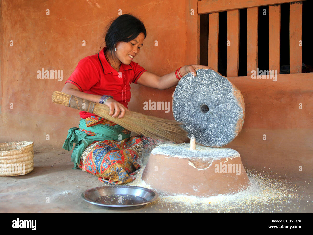 Nepal: woman grinding rice with a stone grinder in a village in the Himalaya mountains - Stock Image
