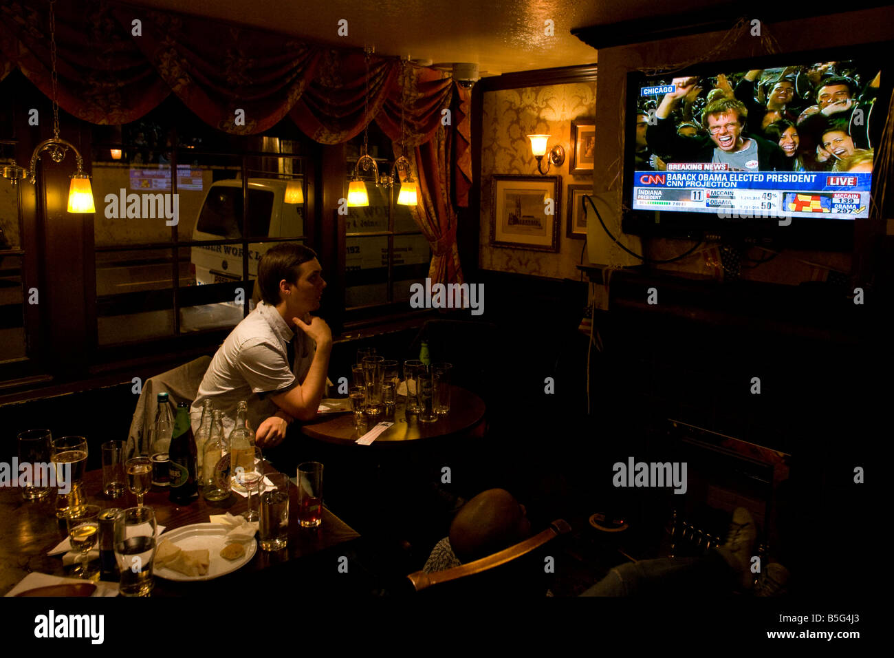 Young man watches TV after Barack Obama is declared Presidential election winner by CNN during overnight party in - Stock Image