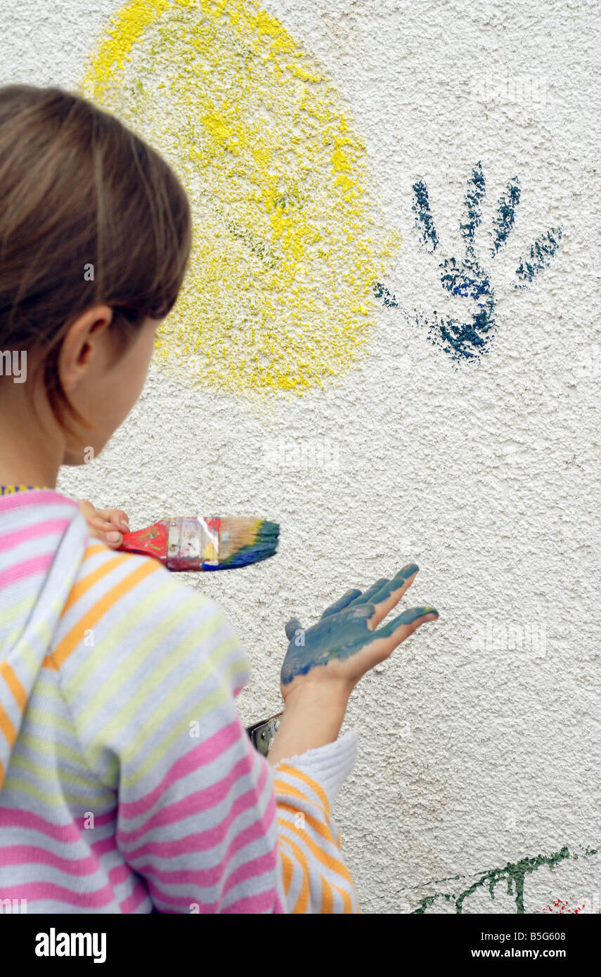 Girl leaving her handprint on a wall - Stock Image