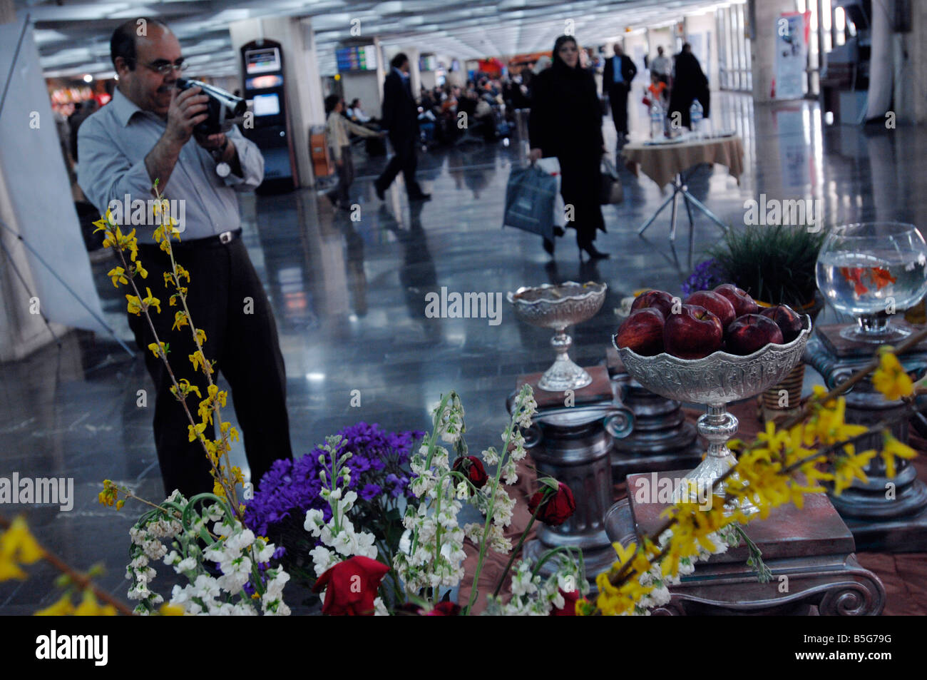 A middle aged Iranian man films a traditional New Year or No Ruz display at Mehrabad Airport - Stock Image