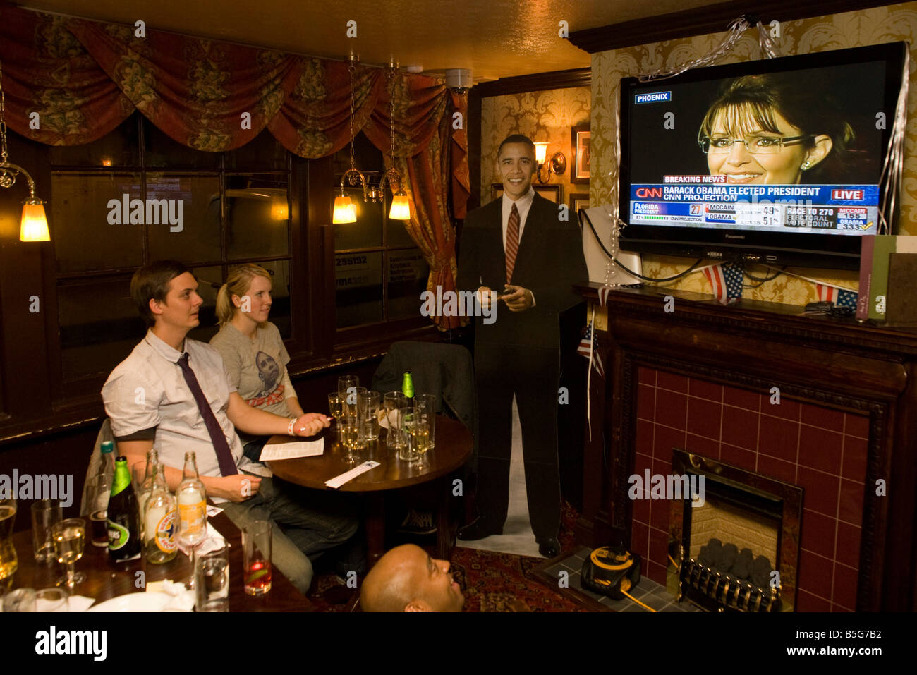 Young couple watch Sarah Palin by life-sized cut-out of Barack Obama during  overnight 2008 election London party - Stock Image