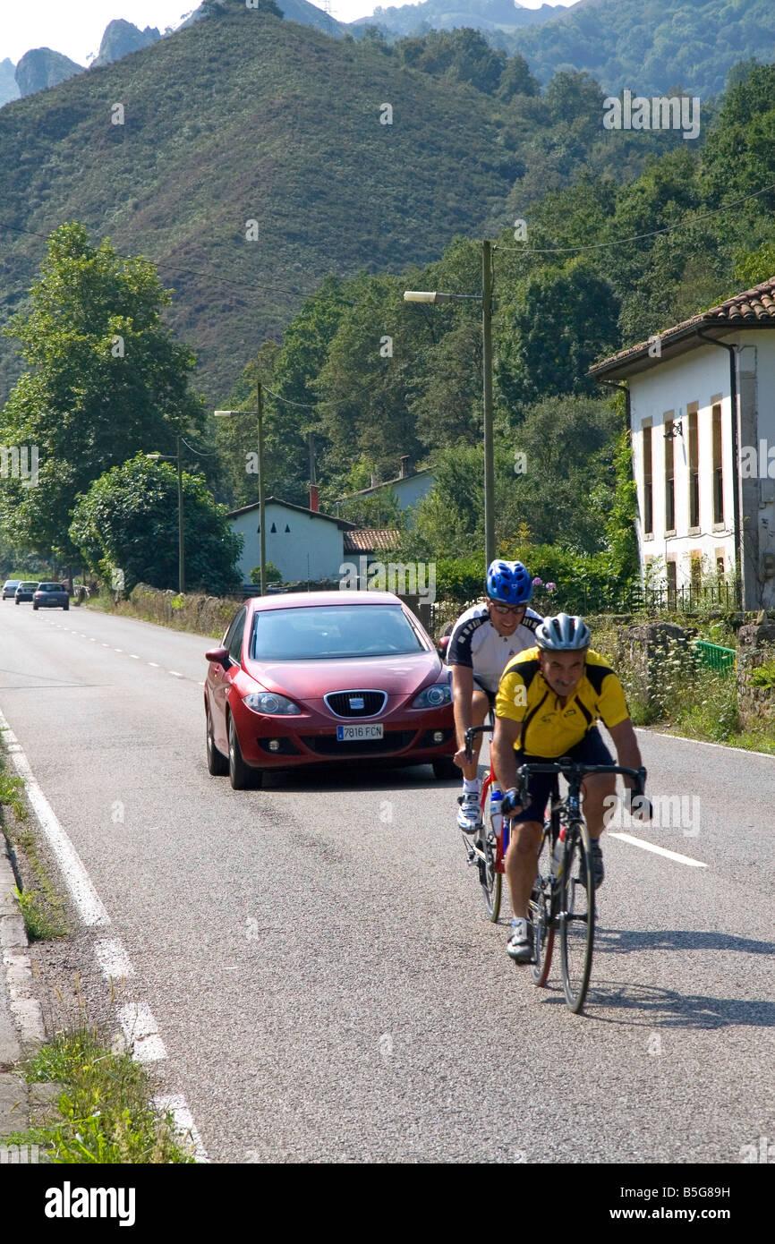 Bicyclists riding through the Picos de Europa near Potes Liebana Cantabria northwestern Spain - Stock Image