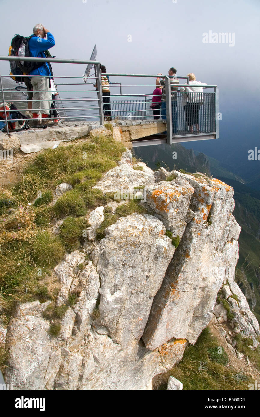 Visitors stand on a platform overlooking the Picos de Europa at Fuente De Liebana Cantabria northwestern Spain - Stock Image