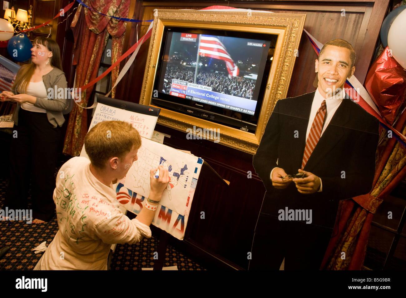 Democrat Party members keep up with latest results with life size cardboard cut out of Barack Obama during 2008 - Stock Image