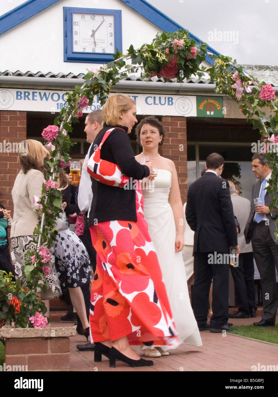 Staffordshire UK August Wedding reception guests standing outside a cricket pavilion - Stock Image