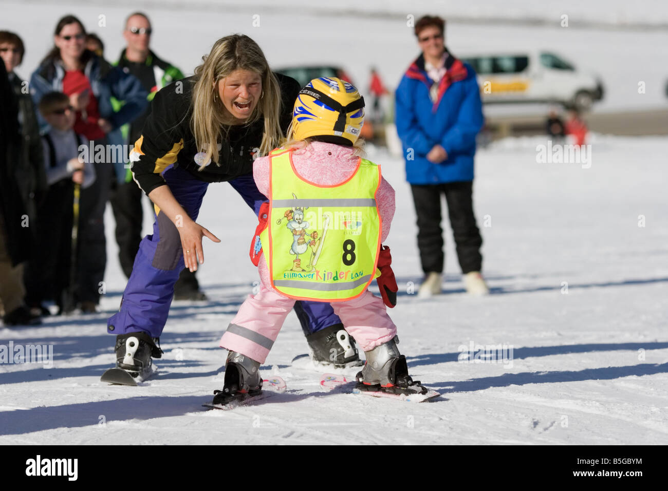 Ski instructor and young child in end of week ski race - Stock Image