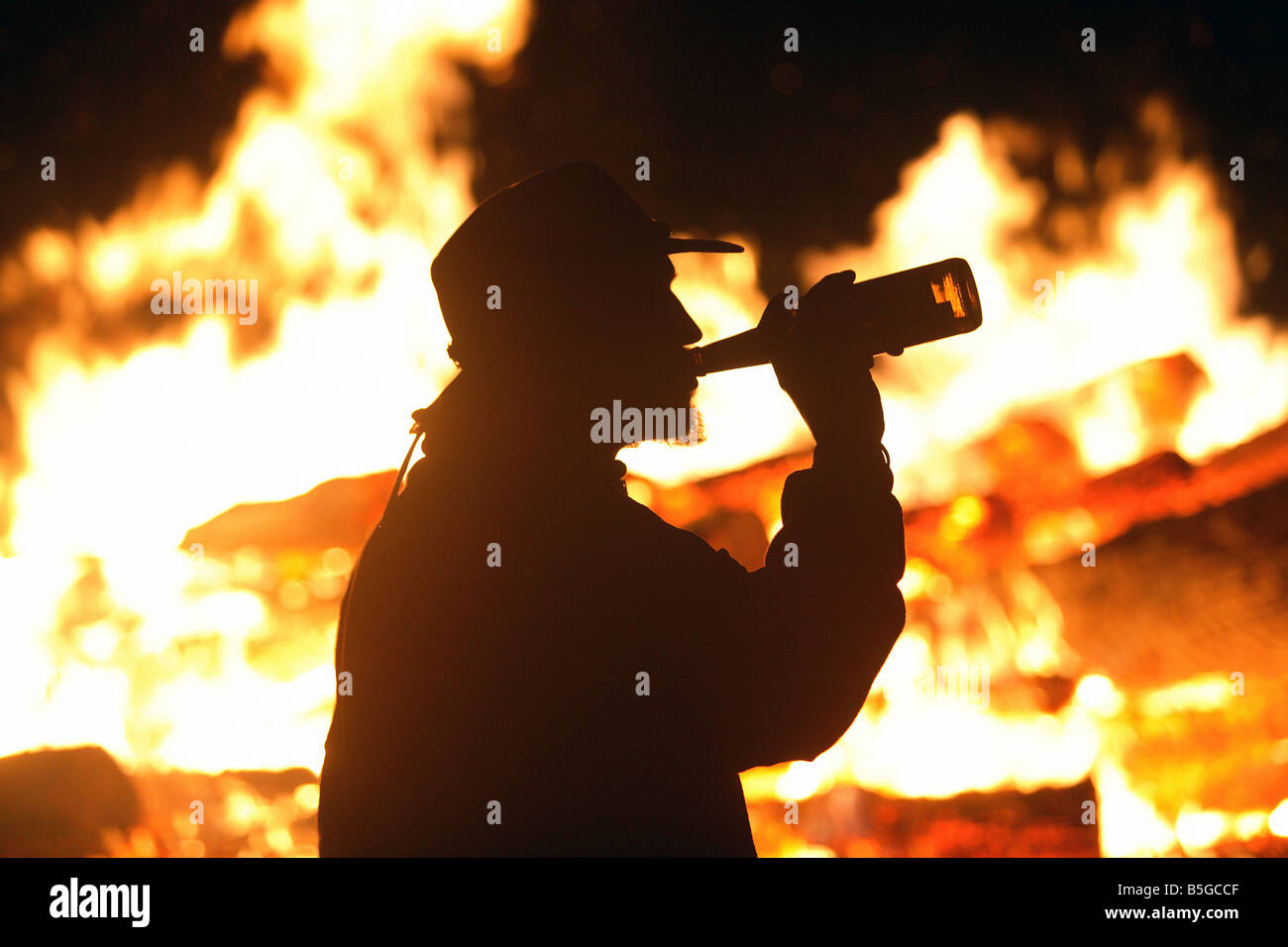Silhouette of a man with a cowboy hat drinking beer near a bonfire - Stock Image