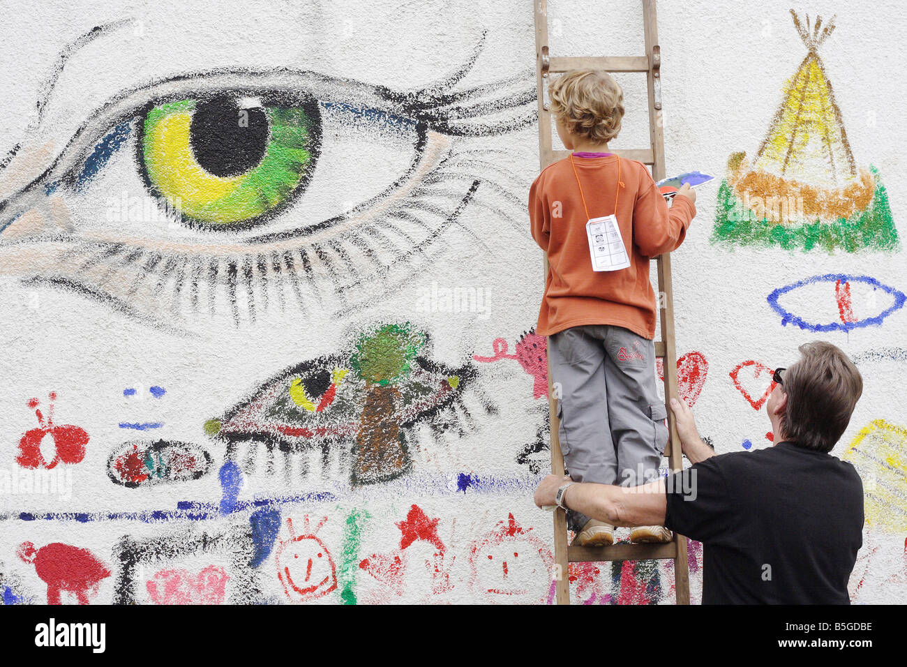 Boy standing on a ladder and painting on a wall - Stock Image