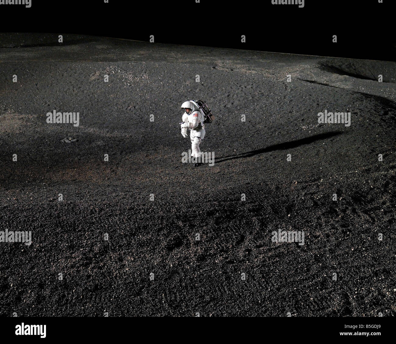 Spacesuit engineer simulates work inside a crater in Johnson Space Center's Lunar Yard. - Stock Image