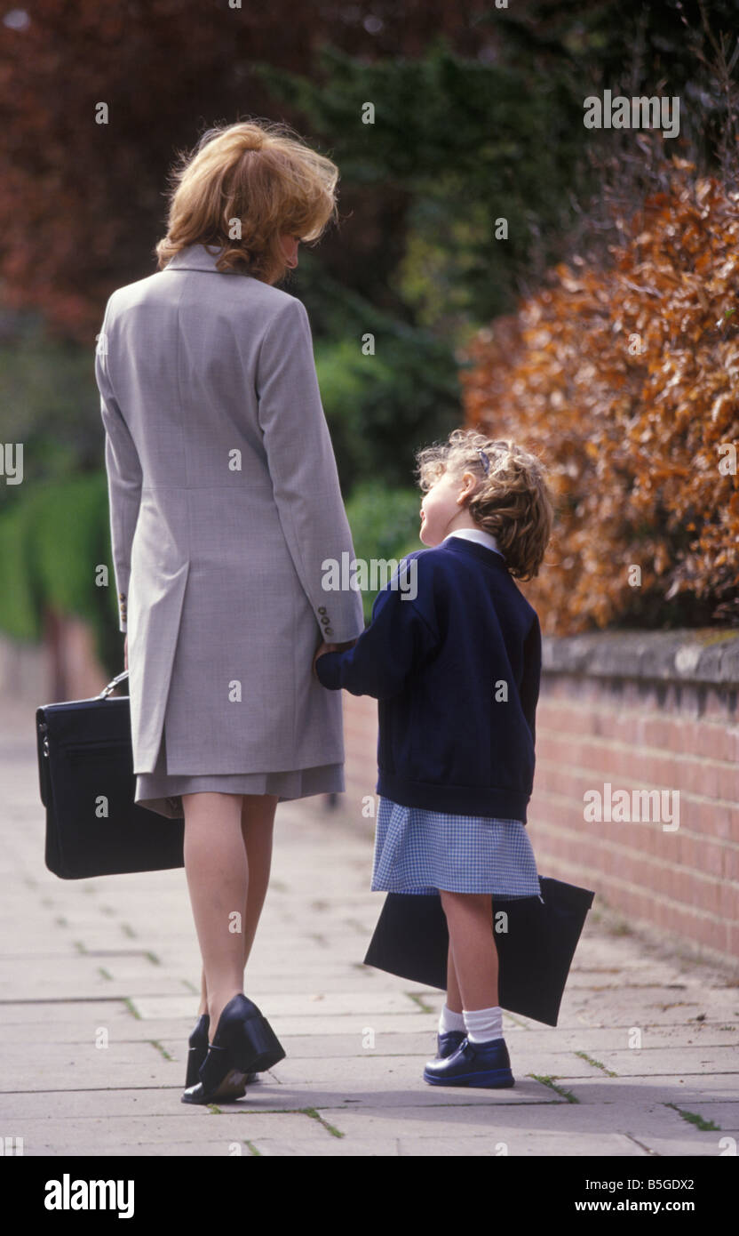 back view of a working mother walking her daughter to school at the start of a new term - Stock Image