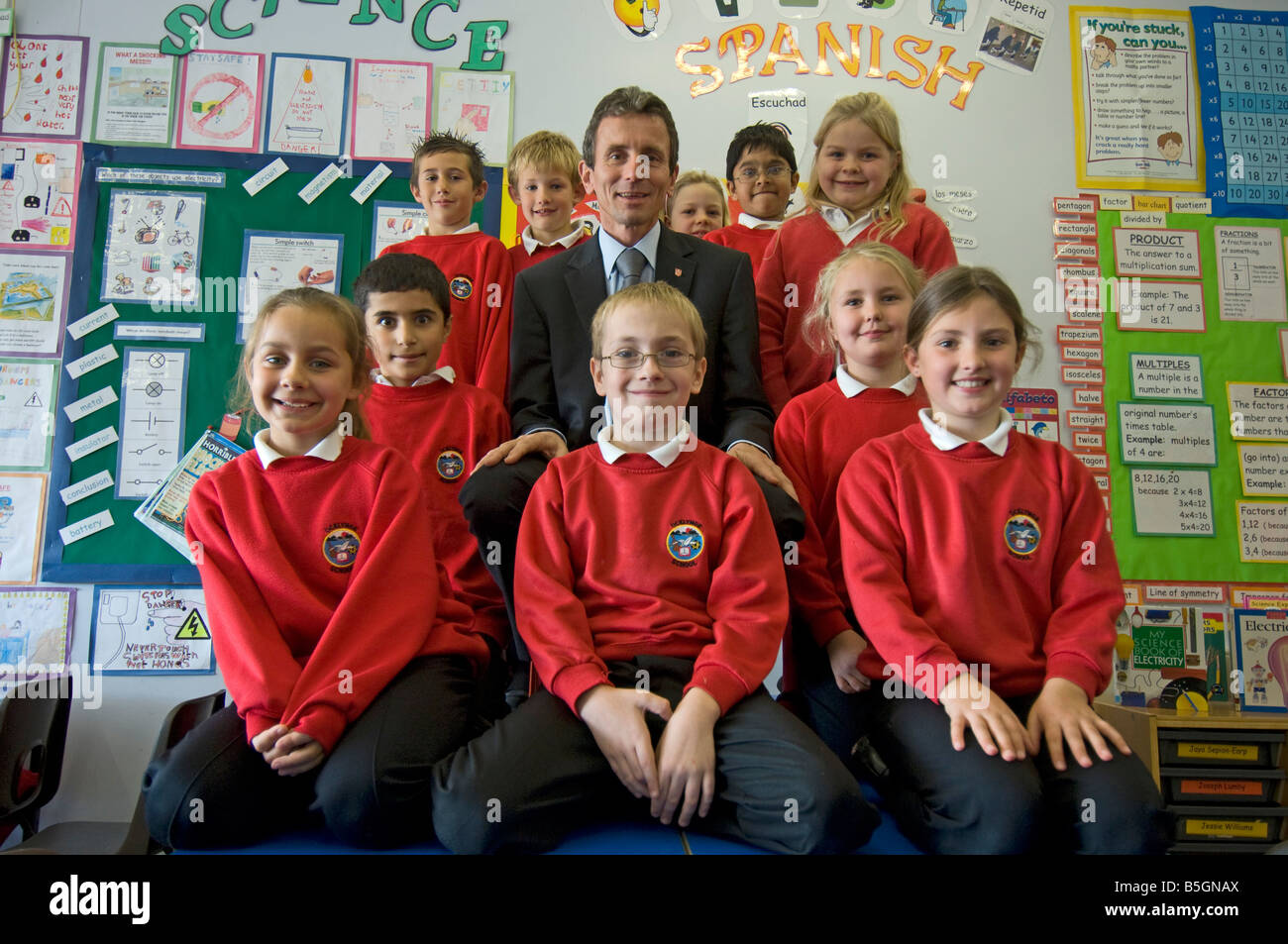 A primary school headmaster with pupils in red uniform sweatshirts in a classroom Stock Photo