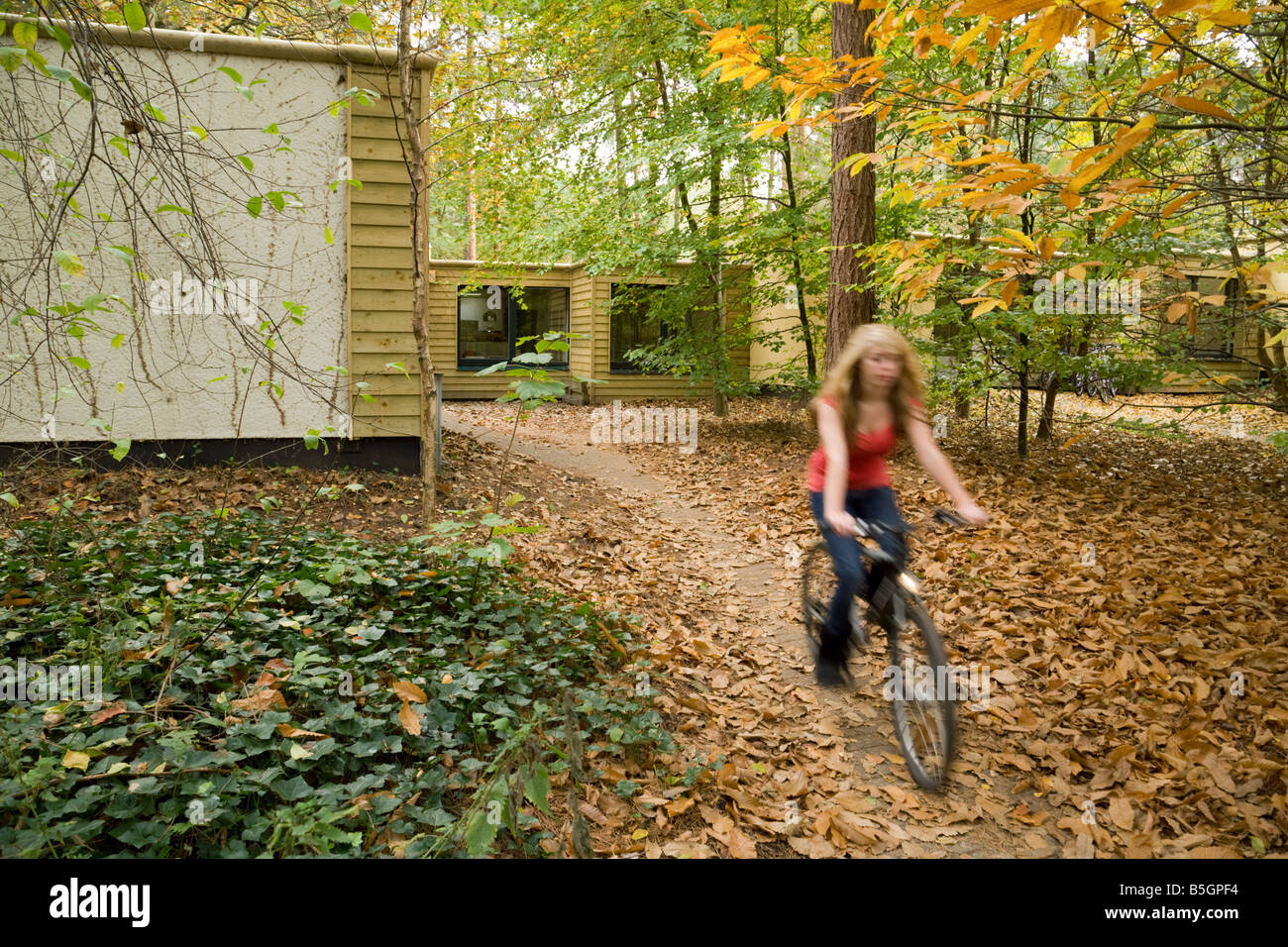 A teenage girl cycles away from her villa, Center Parcs, Elveden, Norfolk, UK - Stock Image