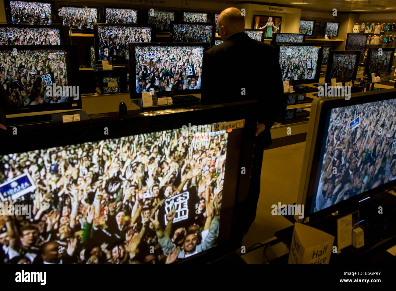 Shopper watches Barack Obama Democrat supporters stage rally seen on BBC News TV screens in John Lewis department - Stock Image