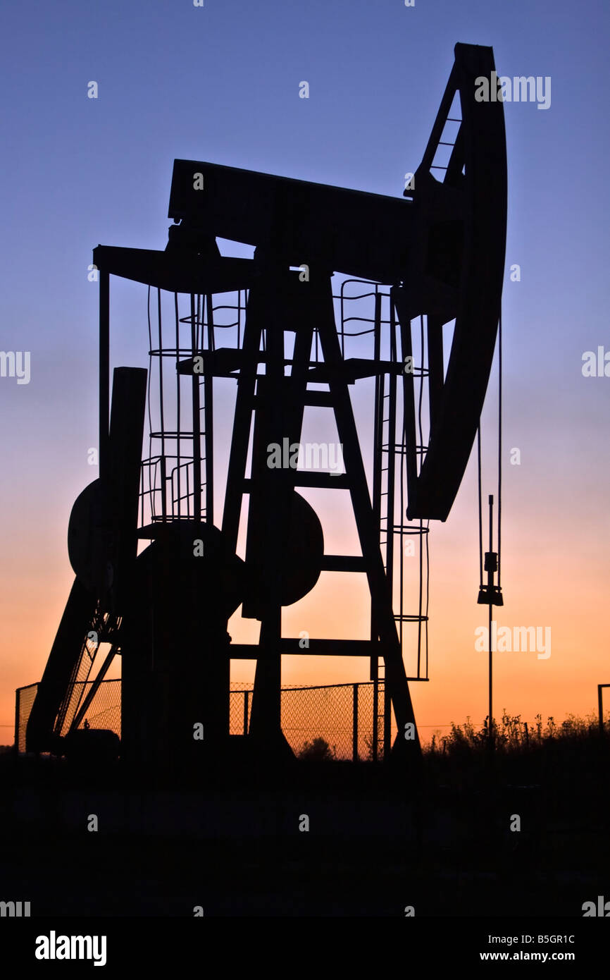 industrial pump jack in the sunset silhouette - Stock Image