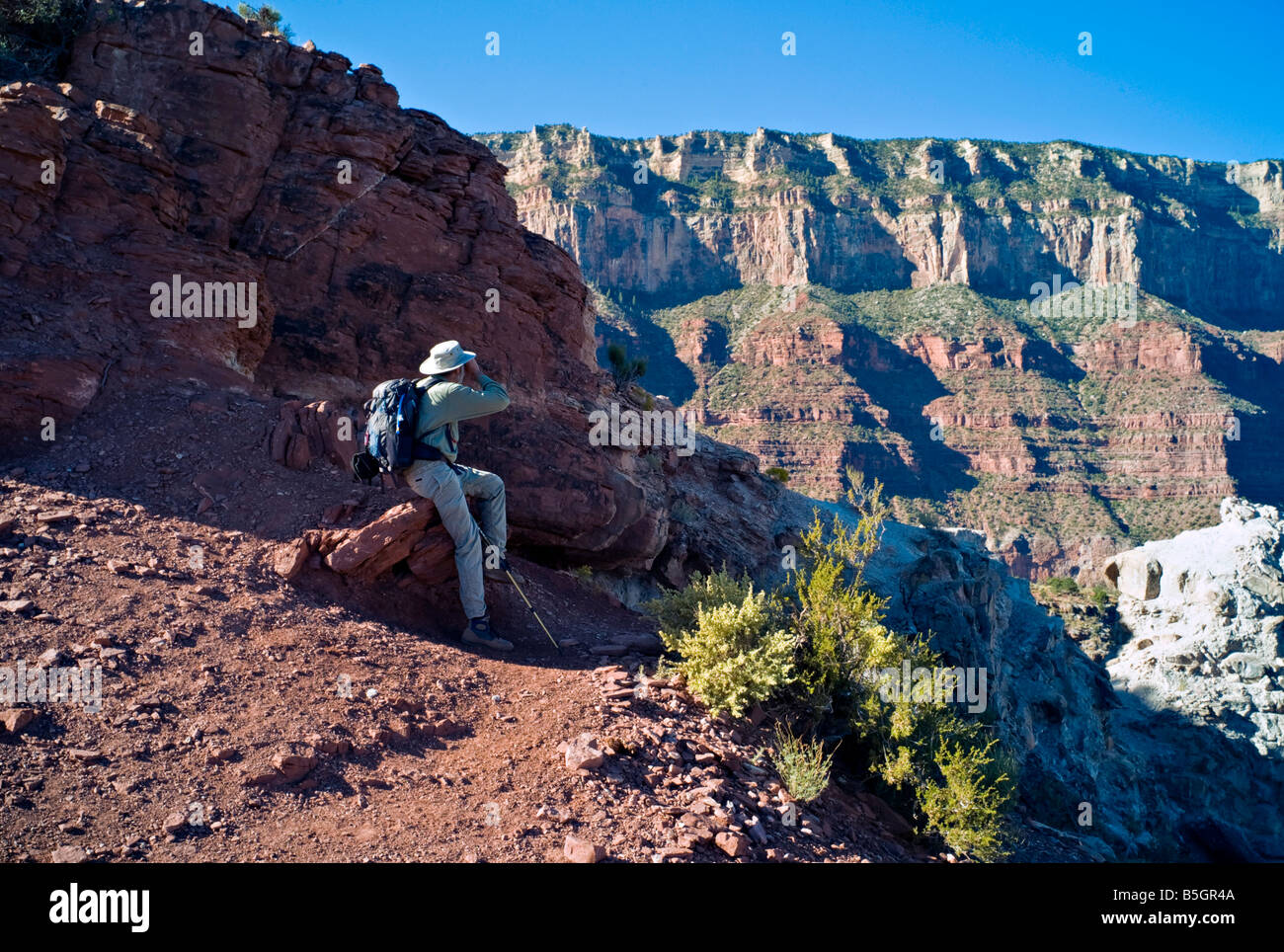 ARIZONA GRAND CANYON Hiker pauses to look at the view as he hikes down the South Kaibab Trail into the Grand Canyon - Stock Image