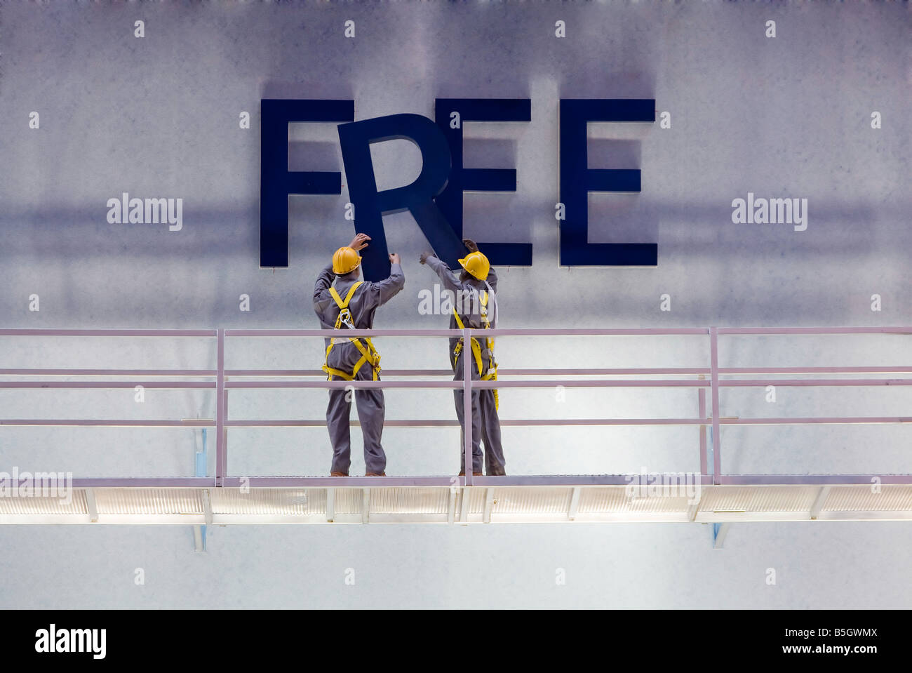 Workers preparing a billboard with the word free while standing on a scaffold - Stock Image