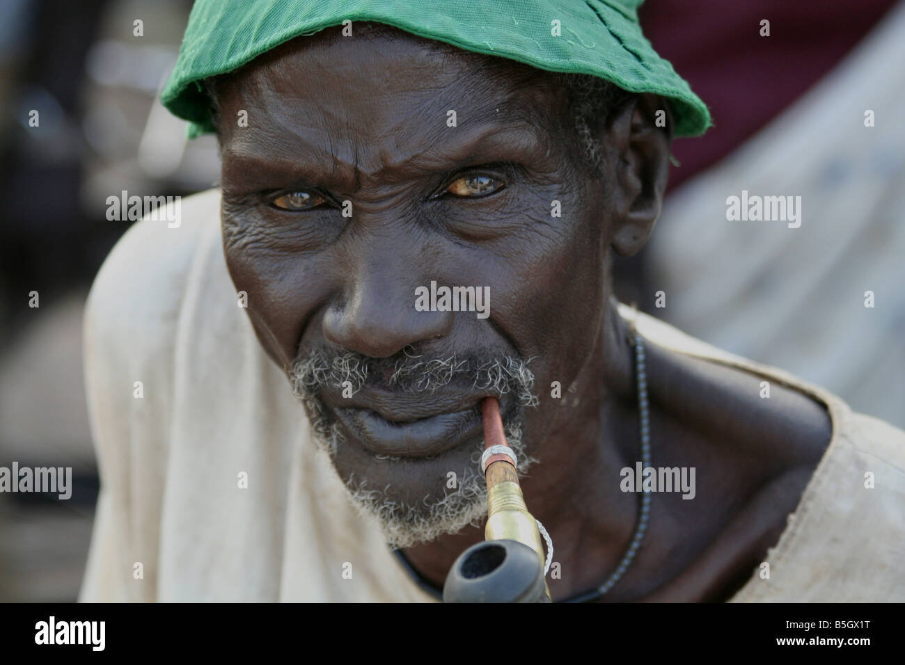 An elderly Dinka man smokes a traditional pipe in Rumbek, South Sudan - Stock Image