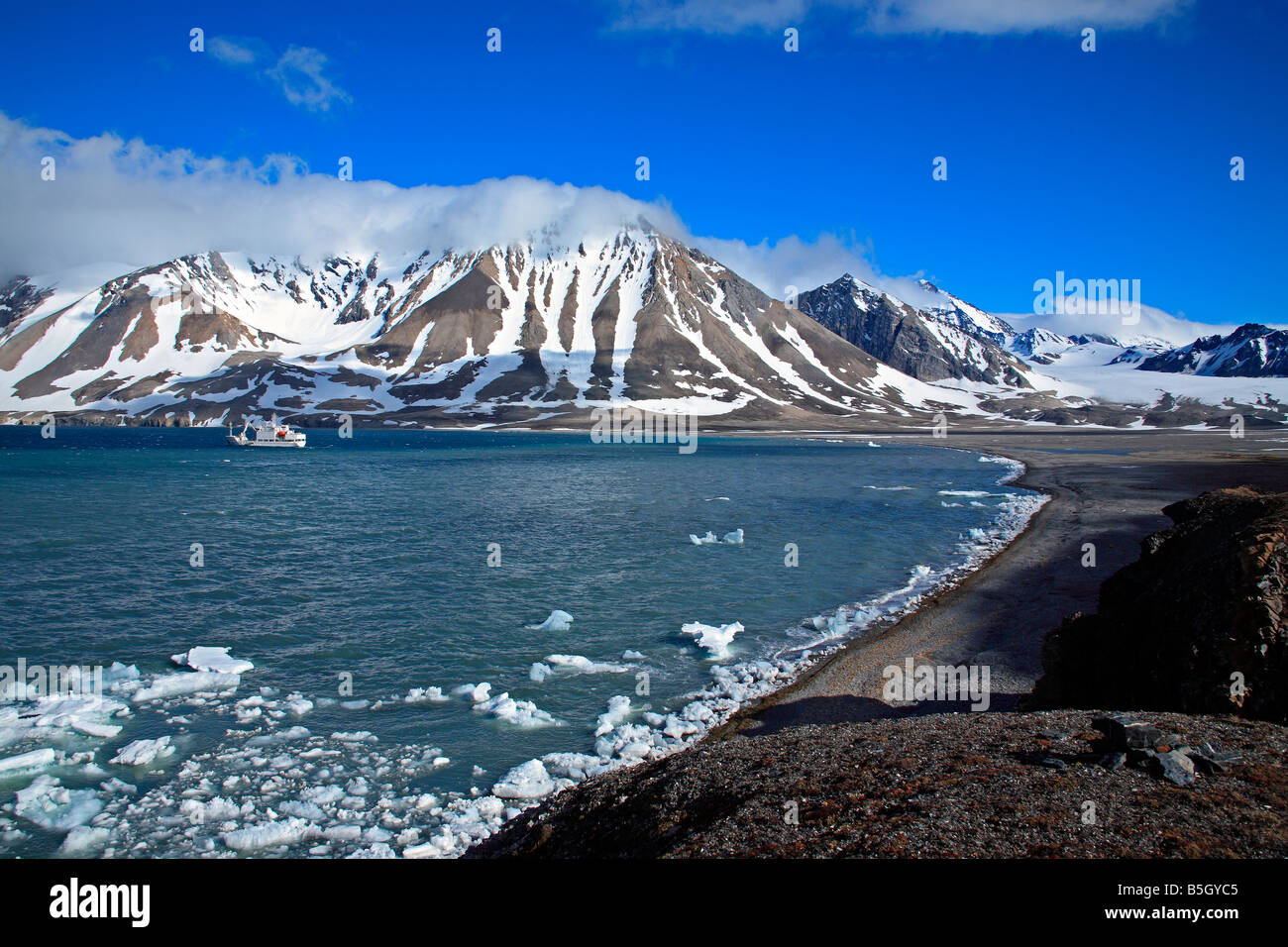 Spitsbergen Snowy Mountains Bay With Ice And Ship Anchored - Stock Image