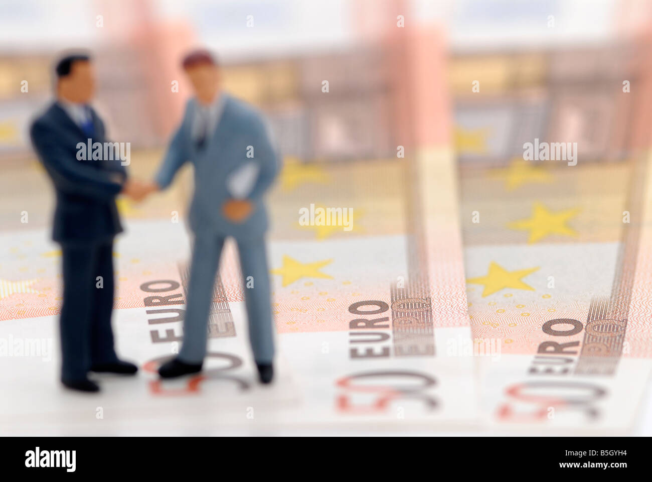 two figures of business men standing upon bank notes Stock Photo