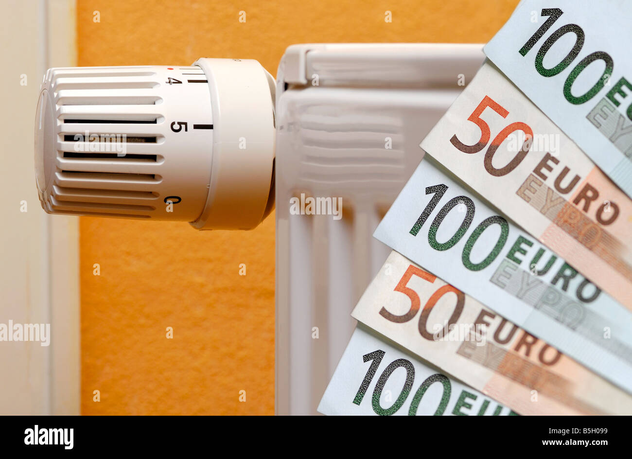 bank notes and a heating, symbol for heating costs - Stock Image