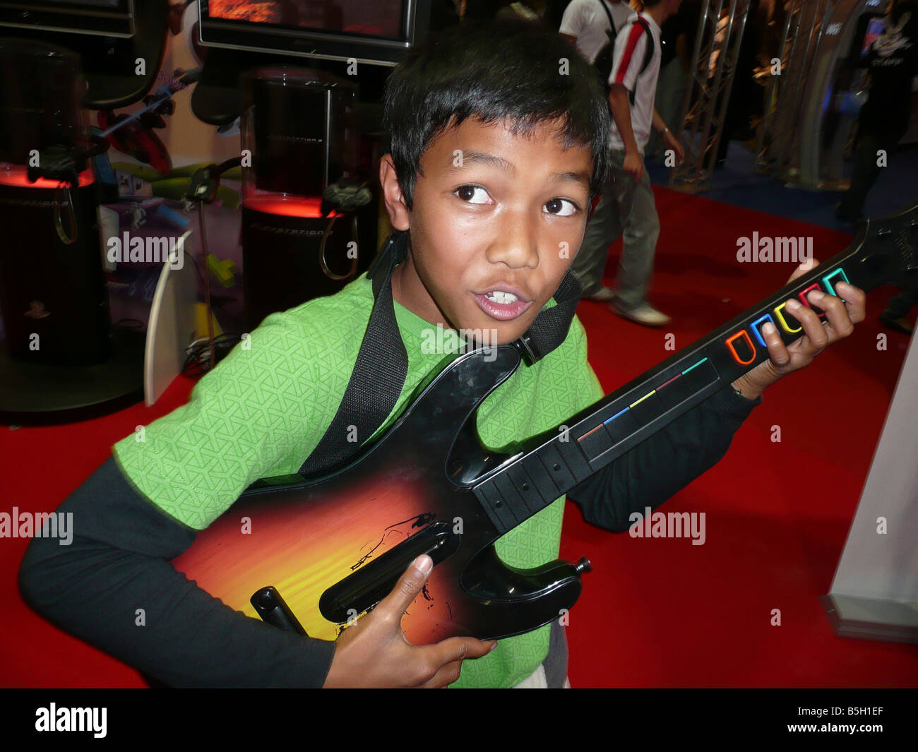 boy playing with Guitar Hero, Sony PS3 - Stock Image