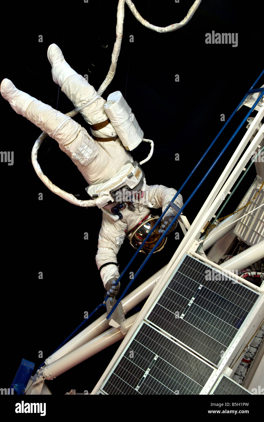 Mock up of astronaut in spacesuit on spacewalk performing maintenance on space station satellite at Houston Space - Stock Image