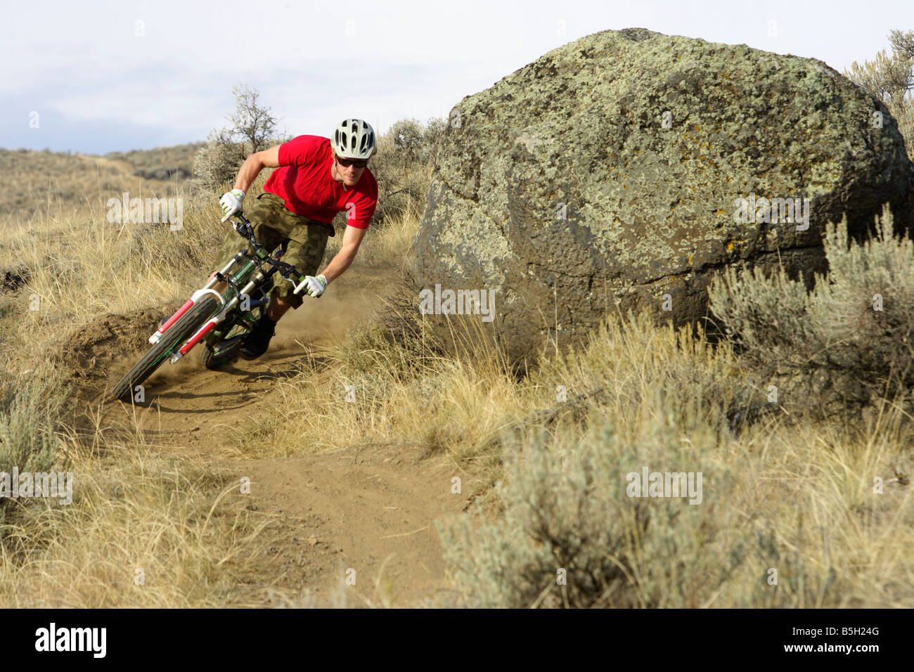 Downhill cyclist driving a turn - Stock Image