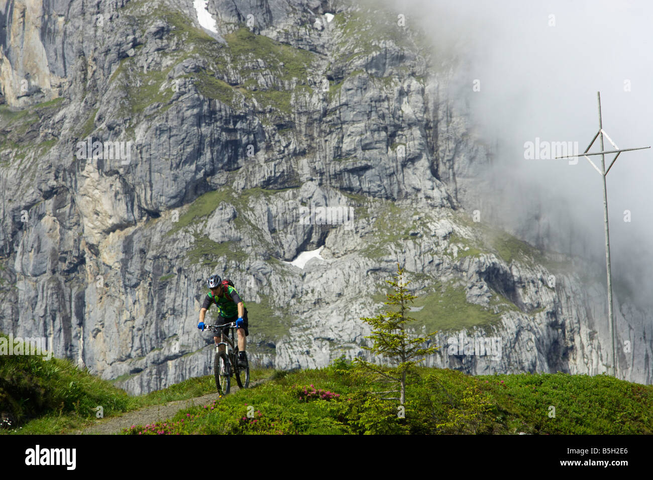 Mountainbike rider in front of a rock face - Stock Image