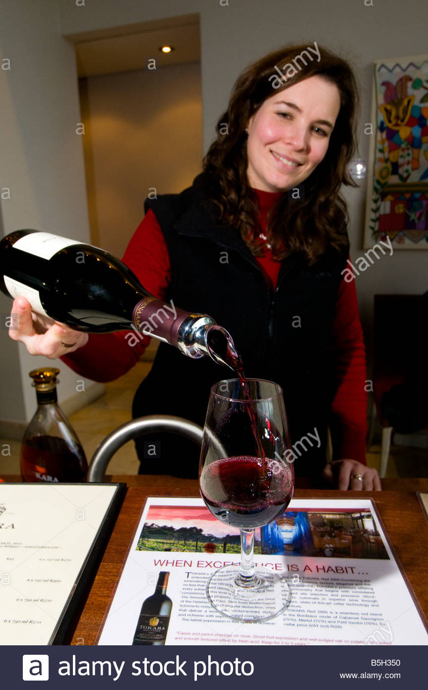 Woman serving wine in the tasting room of the Tokara Winery on Helshoogte Pass near Stellenbosch South Africa - Stock Image