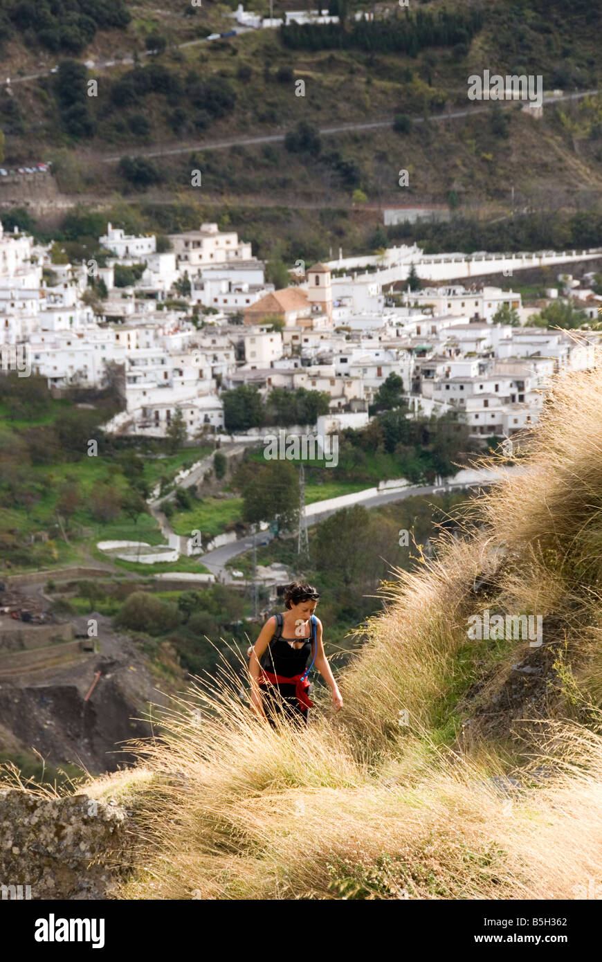 Trekker on trail with view to village of Pampaniera in the Poqueira valley Sierra Nevada mountains in southern Spain - Stock Image